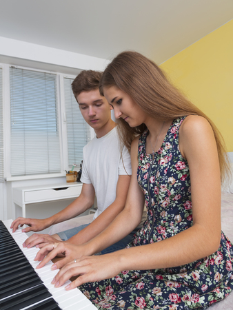 electronic piano: Couple of teenagers playing on electronic piano in the room