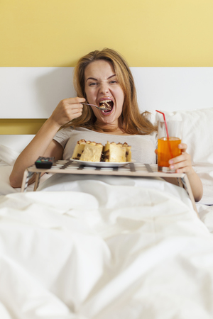 overeat: Teen girl eating cake in bed and watching TV