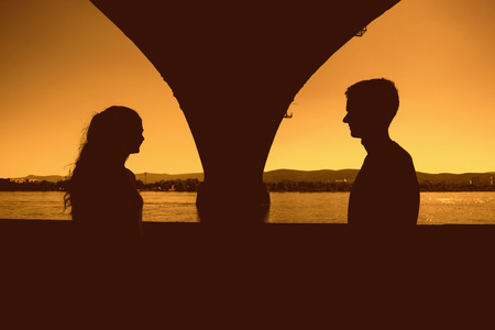 Silhouettes of boy and girl, a date under the bridge