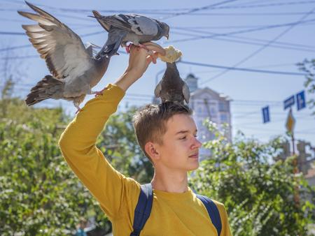feeds: Teen boy feeds pigeons on city street summer day Stock Photo