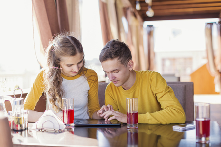 Guy and  girl with  tablet  in a summer cafe expected order photo