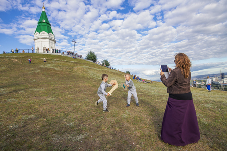 """Krasnoyarsk, Russia - September 03 2016: Mom takes on the tablet as a fight with swords of her children on the food festival """"Summer Kitchen"""" on the mountain Pokrovskaya"""