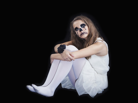 Make-up for the celebration of Halloween, the girl in a white dress on a black background