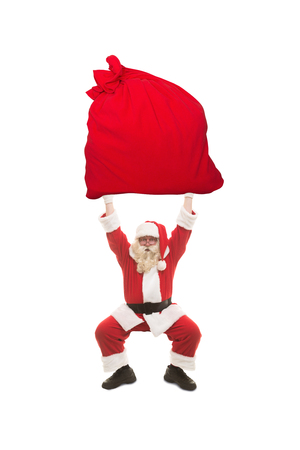 Santa Claus trains to lift very heavy bag with gifts, photo on the white background
