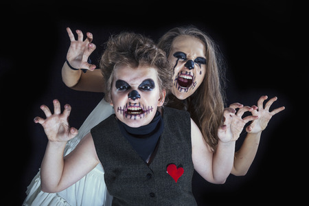 A couple of teenagers, dressed in costumes of the groom and the bride zombies for Halloween celebration photo