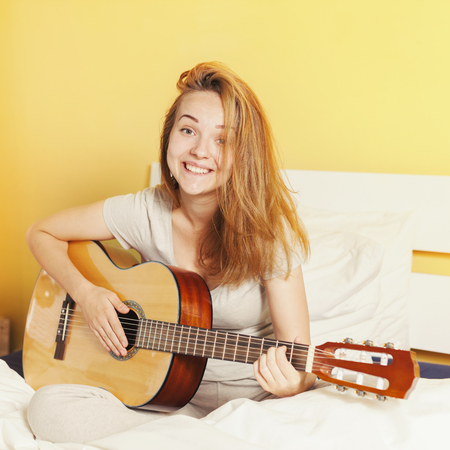 Happy smiling teen girl playing  on guitar on the bed at home photo