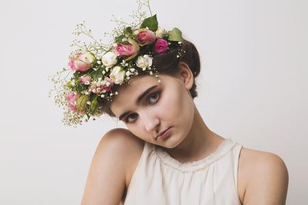 mujer con rosas: Mujer tímida joven en una guirnalda de flores de rosas