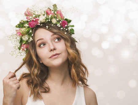 Portrait of a young girl in a wreath of pink and white roses, dreaming about pleasant Stock Photo