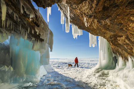 Male tourist with a dog near the ice grotto Olkhon Island on Lake Baikal, winter day Stock Photo