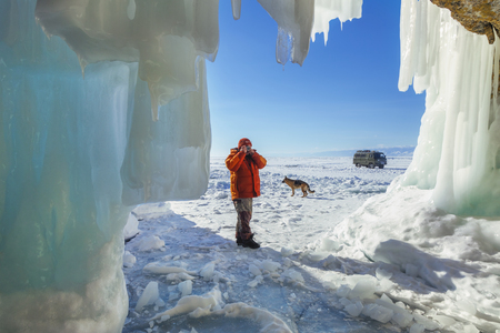 Male tourist photographer with dog near the ice grotto Olkhon Island on Lake Baikal, winter day