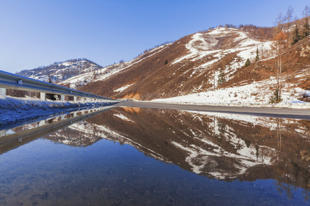 The mountain near the road is reflected in the spring puddle of water, Altai, Russia Stock Photo