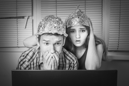 Teens boy and girl in hats made of aluminum foil looking frightened at laptop