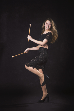 Portrait of a girl with drum sticks on a black background