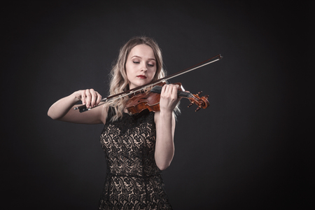 Portrait of a young violinist on a black background Archivio Fotografico