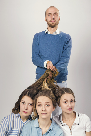 Man holds three young girls by the hair. Stock Photo