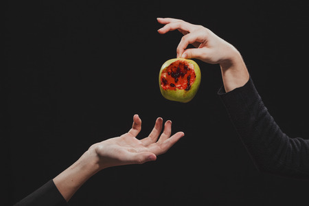 Woman offers  bloody apple to a man,  symbol of dangerous knowledge, close-up, hands Stockfoto