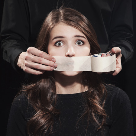 Portrait of a young girl with mouth closed with scotch on a black background