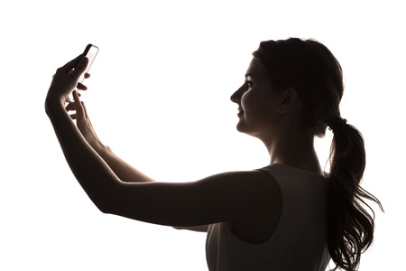 Silhouette of  young girl with a smartphone on a white background 스톡 콘텐츠