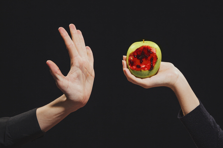 Woman offers  bloody apple to a man,  symbol of dangerous knowledge, close-up, hands Фото со стока