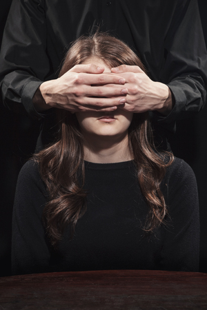 Portrait of a girl on a black background with male hands covering her eyes Foto de archivo
