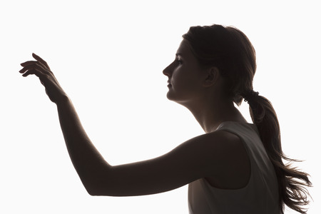 Silhouette of a young girl touching something on a white background