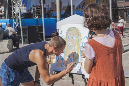 Krasnoyarsk, RUSSIA - August 25, 2018: Man paints  portrait of a girl on  paper, easels and paint are on Mira Street, anyone can draw what wants on day of the 390th  of  founding  Krasnoyarsk Éditoriale
