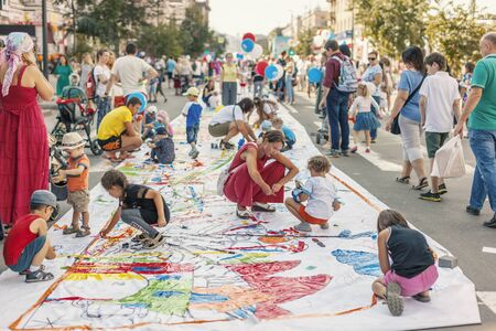 Krasnoyarsk, RUSSIA - August 25, 2018: Young children with parents paint with colorful sticky tape on a banner on of Mira Street on the day of the 390th anniversary of the founding  Krasnoyarsk