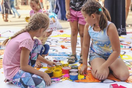 Krasnoyarsk, RUSSIA - August 25, 2018: Little girls paint with colorful sticky tape on a banner on Mira Street on the day of the 390th anniversary of  founding of Krasnoyarsk Éditoriale