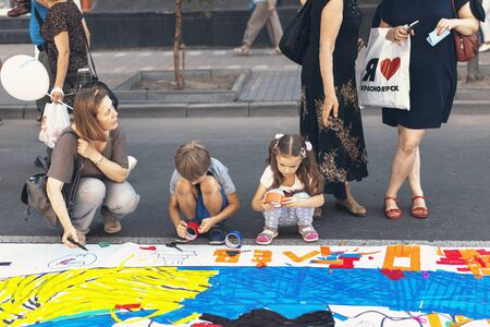 Krasnoyarsk, RUSSIA - August 25, 2018: Little girls with mother paint with colorful sticky tape on a  plastic banner laid out in the middle of Mira Street on day of the 390th of founding Krasnoyarsk