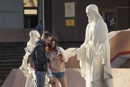 Krasnoyarsk, Russia - June 8, 2019: Girl and a guy near the recently restored sculpture of Christ near the Institute of Arts