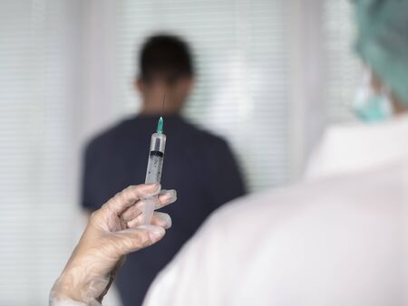 Doctor gives an injection to a patient with a disposable syringe Banque d'images