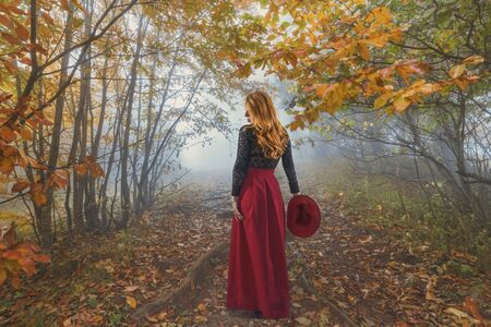 Beautiful red-haired woman with a red hat in the autumn park, photo collage