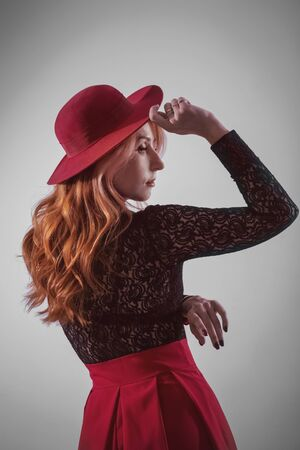 Portrait of a red-haired young woman  in a red hat, profil , studio portrait