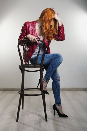 Studio portrait of a young beautiful red-haired woman in a red leather jacket sitting on a bar seat