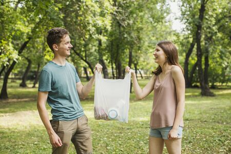 Guy and girl in the park are holding a white plastic bag with purchases in their hands and smiling, looking at each other Banque d'images