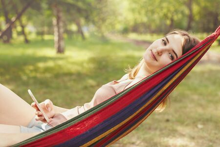Girl resting, lying in a hammock and holding a smartphone Banque d'images