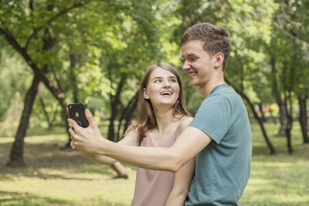 Young couple, boy and girl look at the screen of a smartphone while walking in a park in the summer