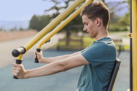 Gym on the street: Young man shakes muscles on a street public fitness machine