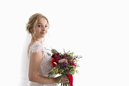 Girl in a white dress, veil and a wedding bouquet in her hands. Bride is getting ready for the wedding