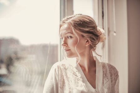 Young beautiful girl in a white peignoir and wedding veil looks out the window