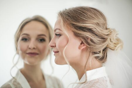 Profile of a smiling bride and her reflection in the mirror