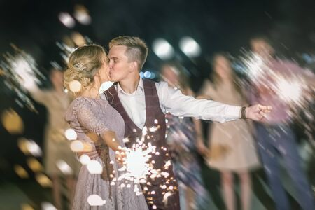 Beautiful wedding kiss, the bride and groom and their guests lit sparklers on the street