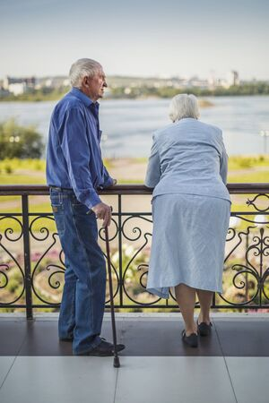 Old man and his woman on a terrace near the river