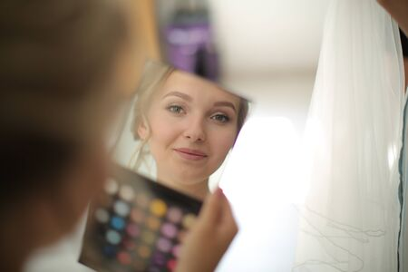 Bride looks in the mirror a palette of eyeshadows and smiles Banque d'images