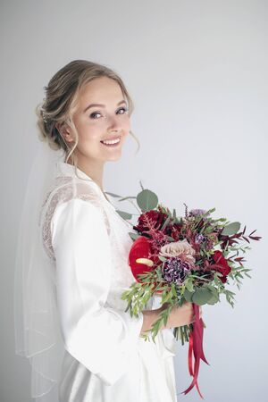 Smiling girl in a white peignoir, veil and a wedding bouquet in her hands. Bride is getting ready for the wedding