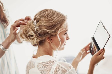 Preparing the bride for the wedding: she looks in the mirror as she is doing her hair Banque d'images