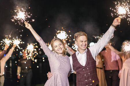 Wedding Finale: A young couple and their guests lit sparklers on the street in the evening