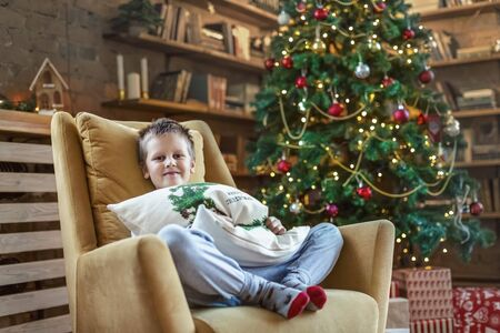 New Year's. Boy sitting in a chair near near a New Year tree with gifts