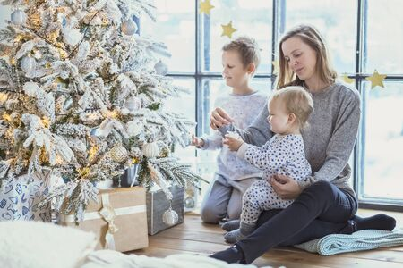New Year's. Mom with children in pajamas near a Christmas tree with gifts in boxes near a large window