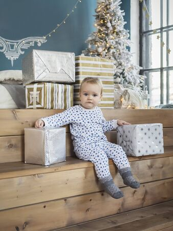 New Year's. Little girl in pajama with gifts in boxes in a room with a Christmas tree. Banque d'images - 139706590